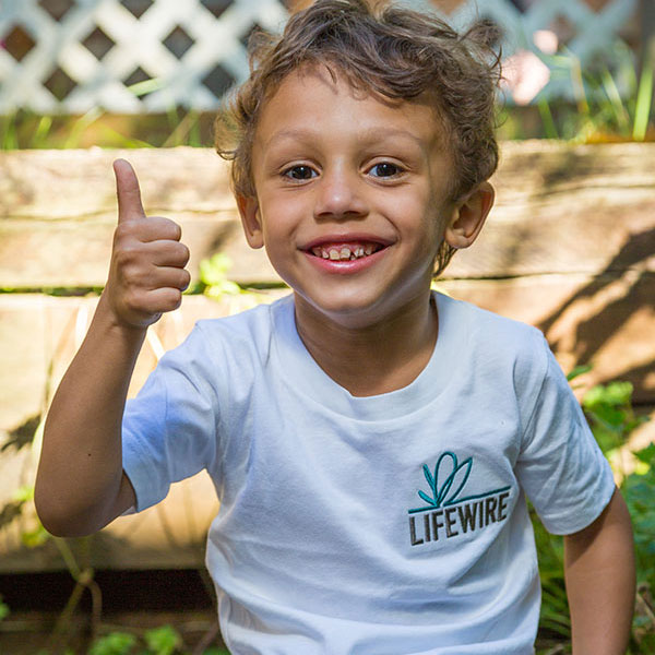 Young boy in a LifeWire t-shirt giving the thumbs-up