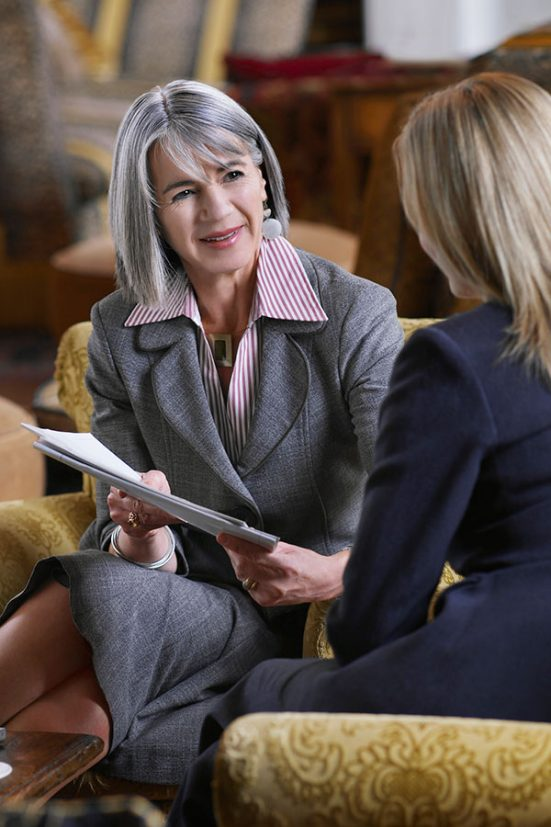 Older corporate woman meeting with a younger woman, reviewing papers