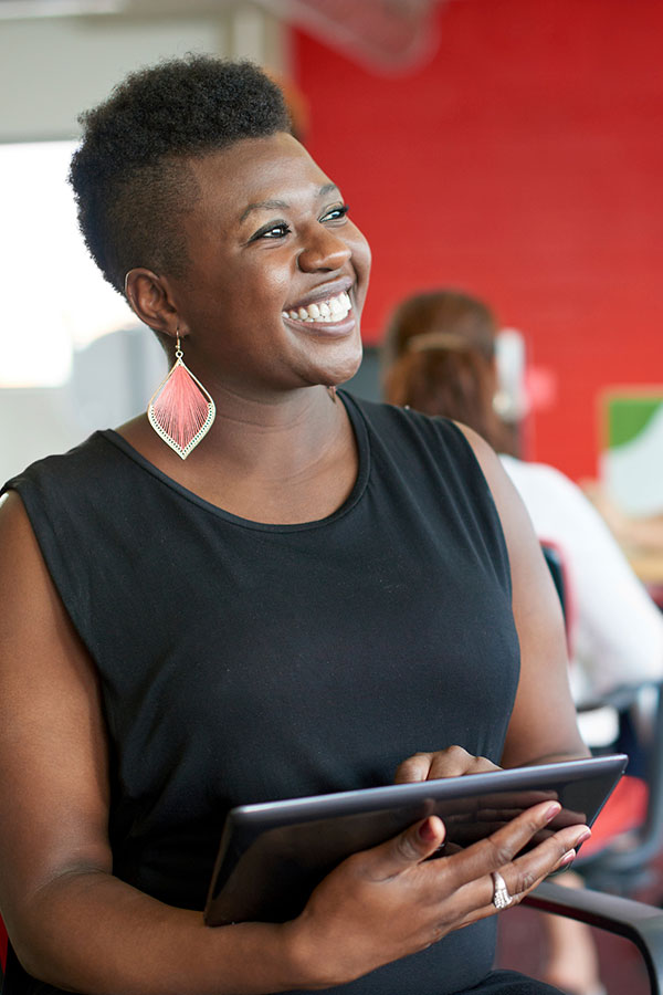 Woman smiling in meeting, holding a tablet device