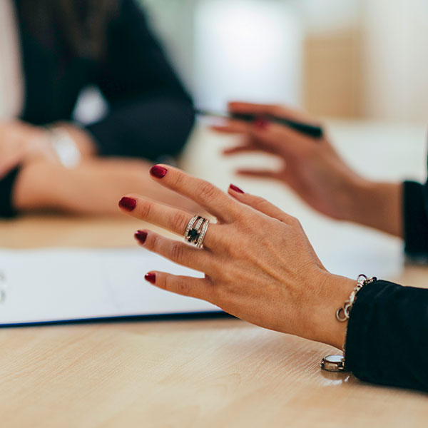 Photo of 2 women's hands in a meeting