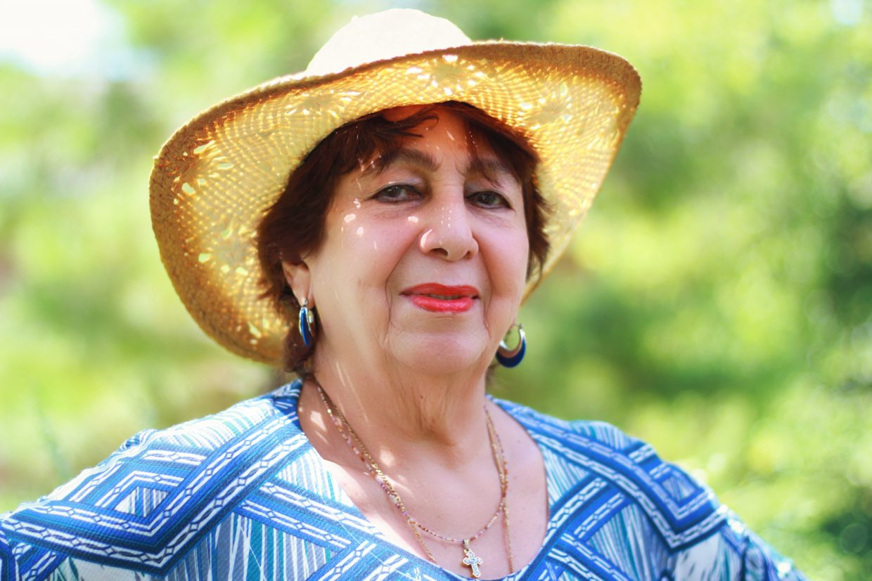 Mature woman looking at camera with woven hat on