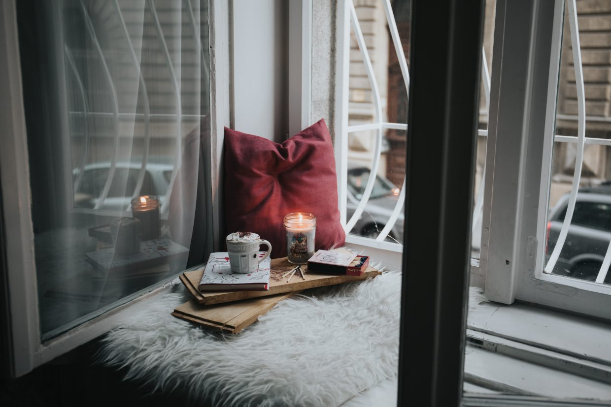 Cozy spot in front of a window with pillow, hot chocolate, candle, and books