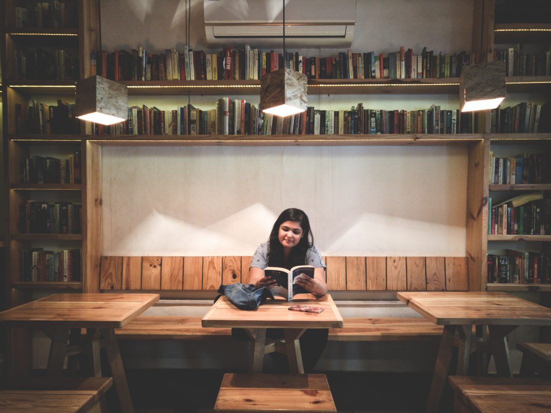 Woman reading at table surrounded by bookshelves