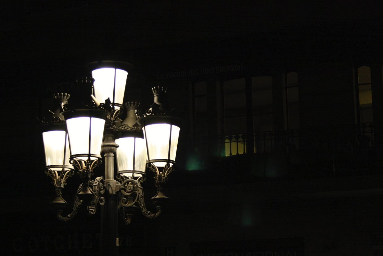 On a dark street a gaslamp shines with five lamps