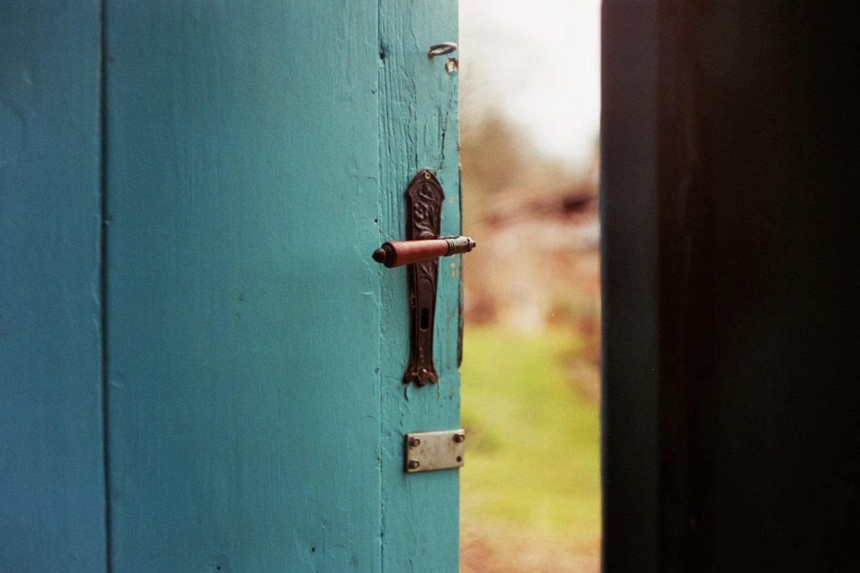 Teal door opening to the outside