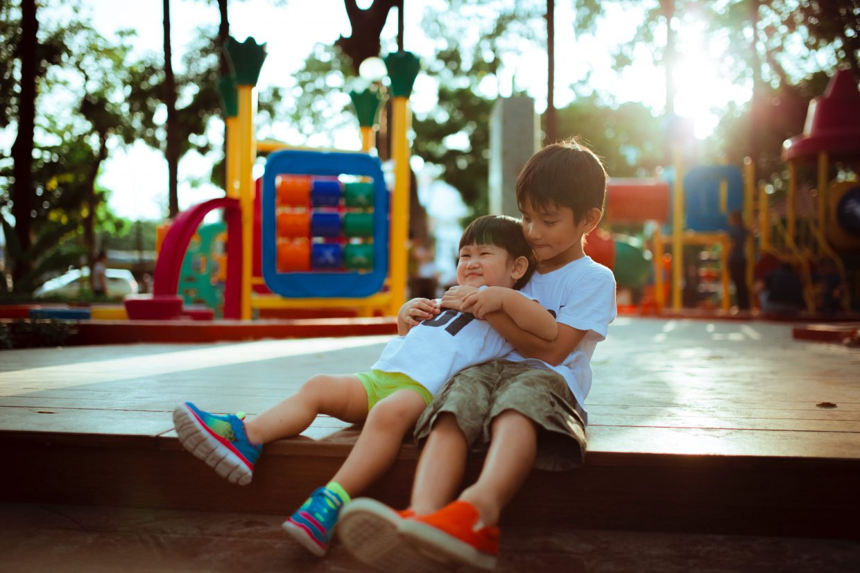 Two boys sitting and hugging on a playground