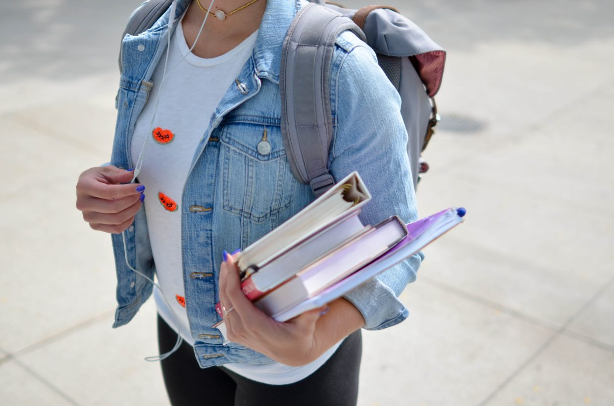 woman holding text books with backpack on