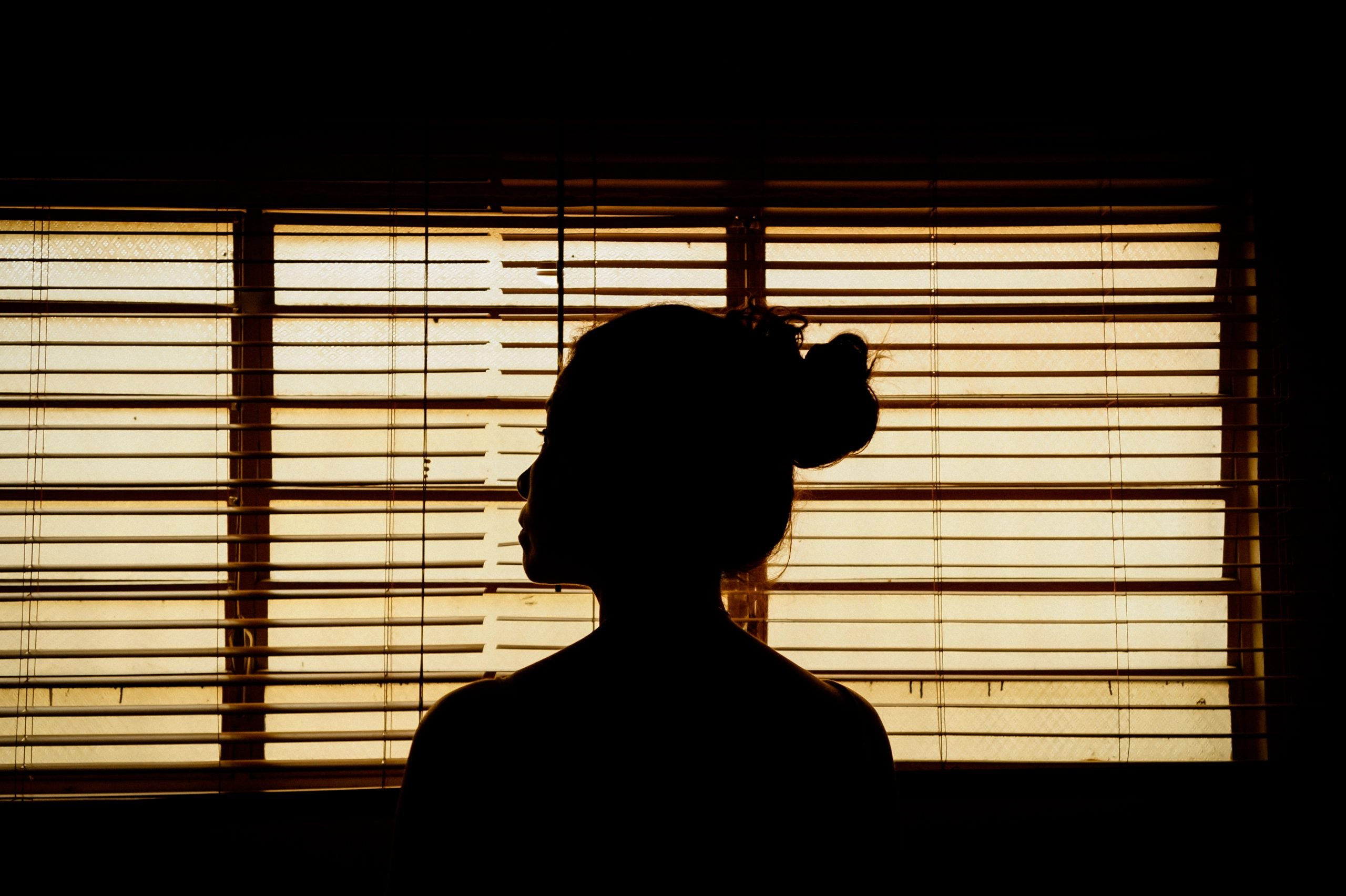 Silhouette of a woman in front of a window with the blinds shut