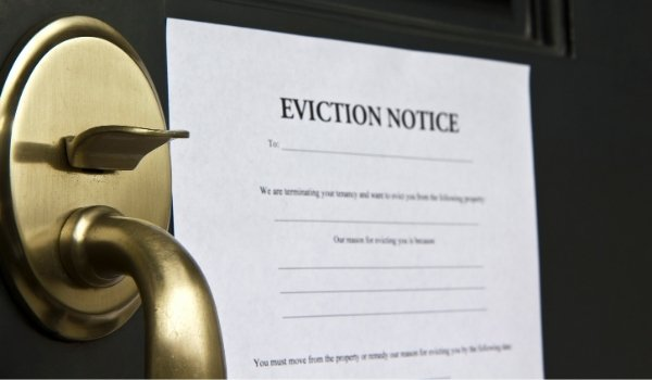 Paper copy of eviction notice on brown front door with brass door handle