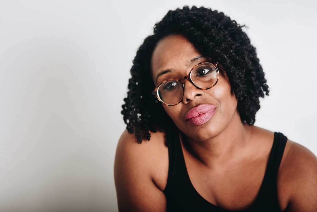 Black woman wearing black tank top and glasses looks sadly in the distance.