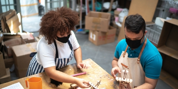 Long curly-haired black woman wearing a black mask, white shirt, and striped apron leans over a wooden table to look at a toy airplane while white man wearing a black mask, turquoise shirt, and tan apron holds a toy airplane.