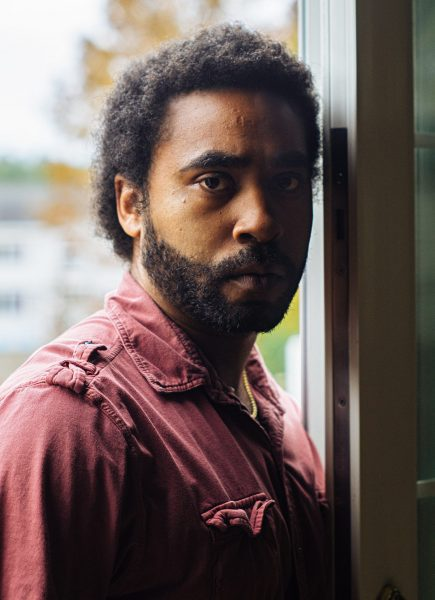 Black man with medium length curly hair and short beard with gold chain and redish button down shirt stands in doorway
